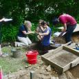 Five people engaged in an archaeological dig at the Emily Dickinson Museum