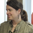 Closeup of Pascha Bueno-Hansen wearing a greenish jacket and hoop earrings, looking off to her right and smiling