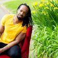 Jericho Brown sitting in a red chair near a patch of flowers and grass