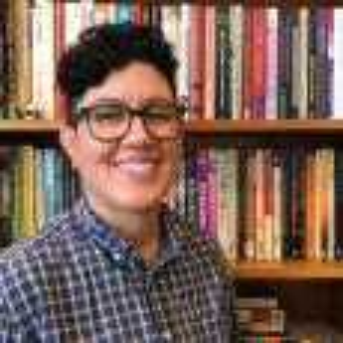 Marisol Lebrón in front of a bookshelf, smiling