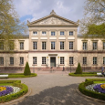 Göttingen Abend building, in front of which are trees, neatly manicured gardens and benches