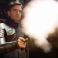 Image of a man in a suit of armor, firing a weapon that is emiting a cloud of white smoke