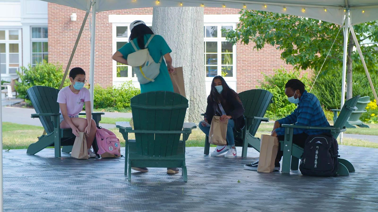 Four masked students eating outside under a canopy.