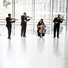 Juilliard Quartet, standing and playing their instruments