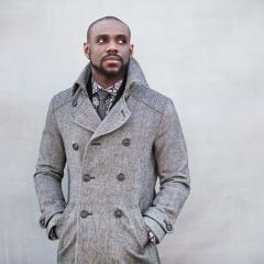 Omar Thomas standing with his hands in the pockets of his double-breasted gray coat