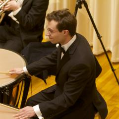 Young man in a suit and tie playing timpani on the Buckley Recital Hall stage