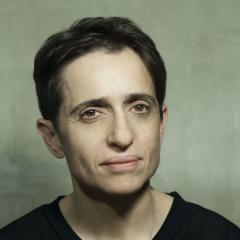 Closeup of Masha Gessen wearing a black T-shirt