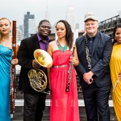 The five members of Imani Winds standing outdoors nin front of a cityscape, dressed colorfully and holding their instruments