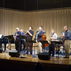 Faculty members onstage playing piano, saxophones and other instruments, behind music stands and electronic speakers