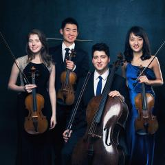 The Omer Quartet dressed formally, posing with their stringed instruments