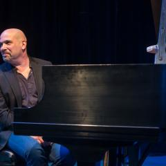 Eugene Uman sitting at a piano on a stage