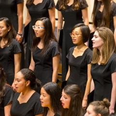 Young women dressed in black, singing on the Buckley Recital Hall stage