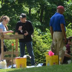 Four people engaged in an archaeological dig at the Emily Dickinson Museum