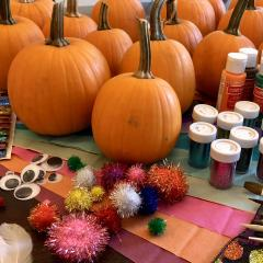 Pumpkins displayed with decorating supplies including paint, glitter, brushes, googly eyes, pom poms, tissue paper, sequins, feathers, and ribbon