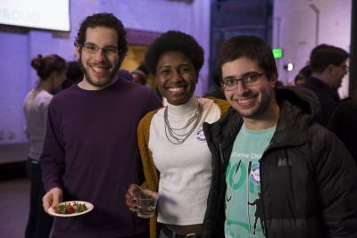 three students at a party, smiling and posing for the photo