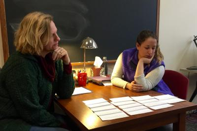 An instructor and a student look at writing samples spread out on a table