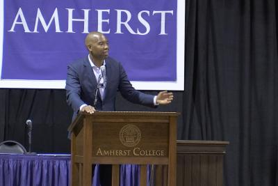 Ta-Nehisi Coates speaking at a podium at Amherst College