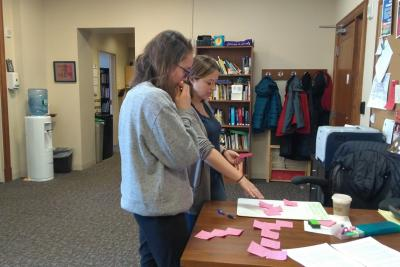 A student and a writing associate organize the parts of an essay using white boards and sticky notes.