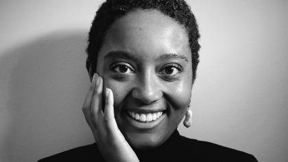 A photo of a Black woman smiling and holding her hand to her face.