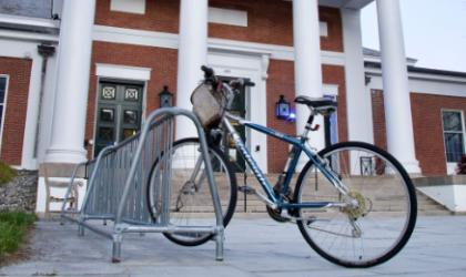 A bicycle parking in front of a building with white columns