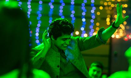 A young man dancing in green light
