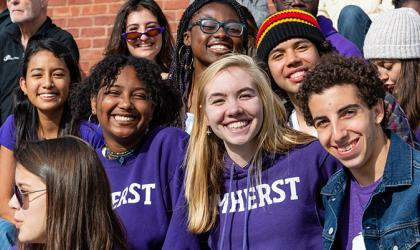 A group of students in Amherst College apparel in the crowd of a football game