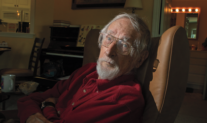 An older man with a white beard sitting in a chair in a dark apartment