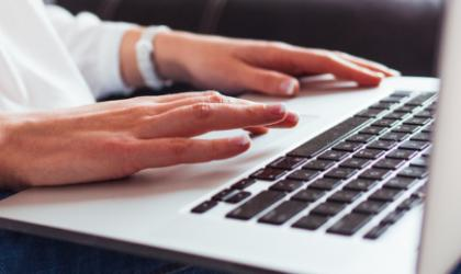 A person's hands typing on a laptop keyboard