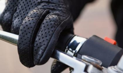 A gloved hand holding onto a motorcycle handle