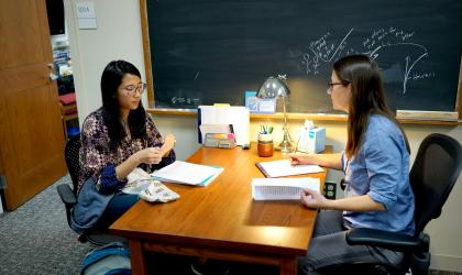 student and writing associate sit facing each other, with papers on the desk in between