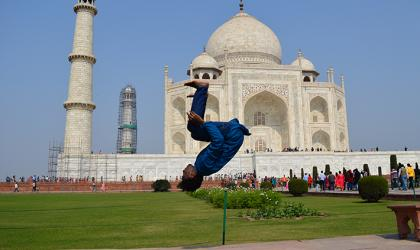 A person doing a backflip in front of the Taj Mahal