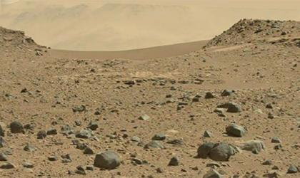 A photo of the surface of Mars with red dirt and mountains