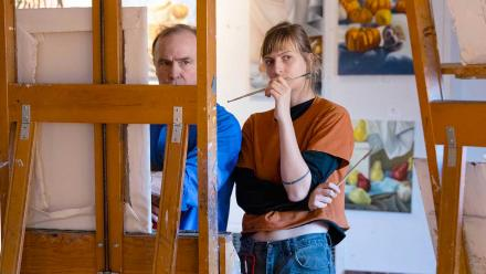A faculty member and a student working together at an easel