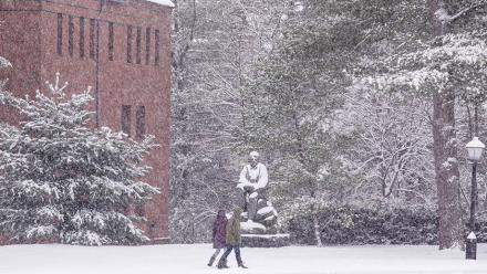 Amherst students walking on a snowy day past a statue of Robert Frost on the campus of Amherst College.