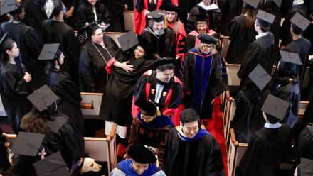 Faculty and students wearing regalia exit Johnson Chapel after a senior awards ceremony