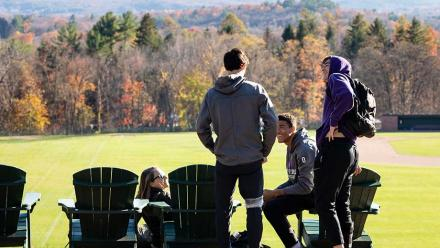 Four people gathered at Adirondack chairs overlooking Memorial Hill