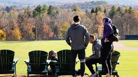 Students gather around Adirondack chairs facing the Mt. Holyoke range
