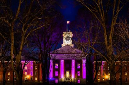 exterior of Johnson Chapel at night, lit by purple lighting