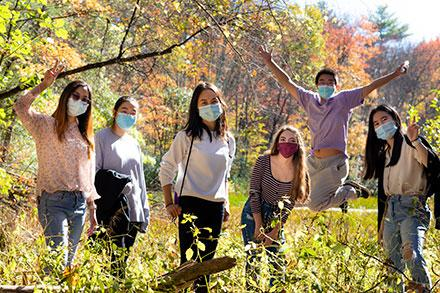 six students in masks pose together on a wildlife sanctuary trail on the Amherst College campus during Mammoth Day