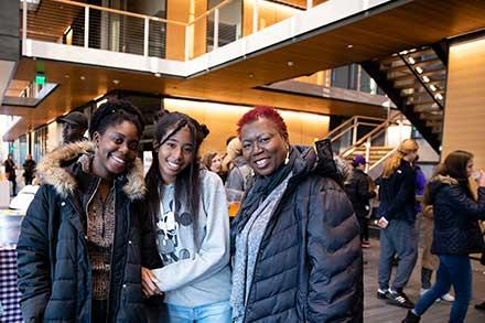 Three women pose for a photo during a reception in the Science Center