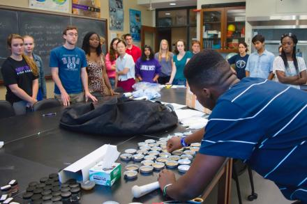 a student demonstrates a procedure in a lab, observed by a large group of students