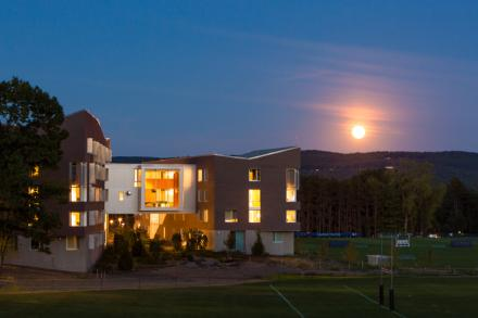 greenway dorms at night with a full moon rising over the mountains