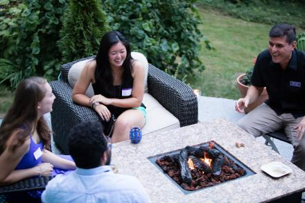 Group of people around an outdoor fireplace
