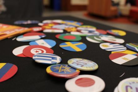 A table covered in a black tablecloth is scattered with a number of badges/pins. Each pin has the design of a country's flag on it. In the middle of the pile is a badge with the CISE logo on it.
