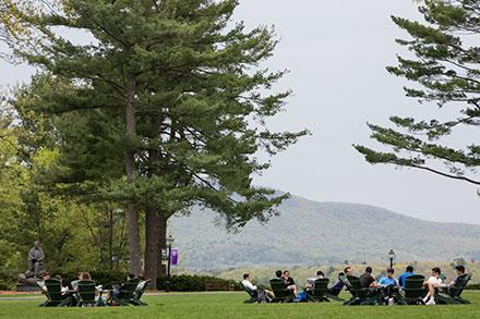 Students sitting in adirondak chairs on the academic quad, Amherst College