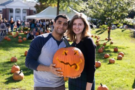 two students pose holding a carved pumpkin