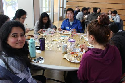 Students sit at a table, eating food. A young woman of South Asian background smiles at the camera in the foreground. At the back of the table, a young man of East Asian background also smiles at the camera.