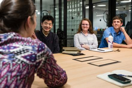 smiling students around a conference table