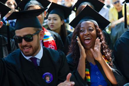 graduating students in regalia cheering