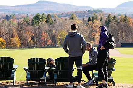 Students gather around Adirondack chairs. A view of Mt Holyoke Range is in the background.